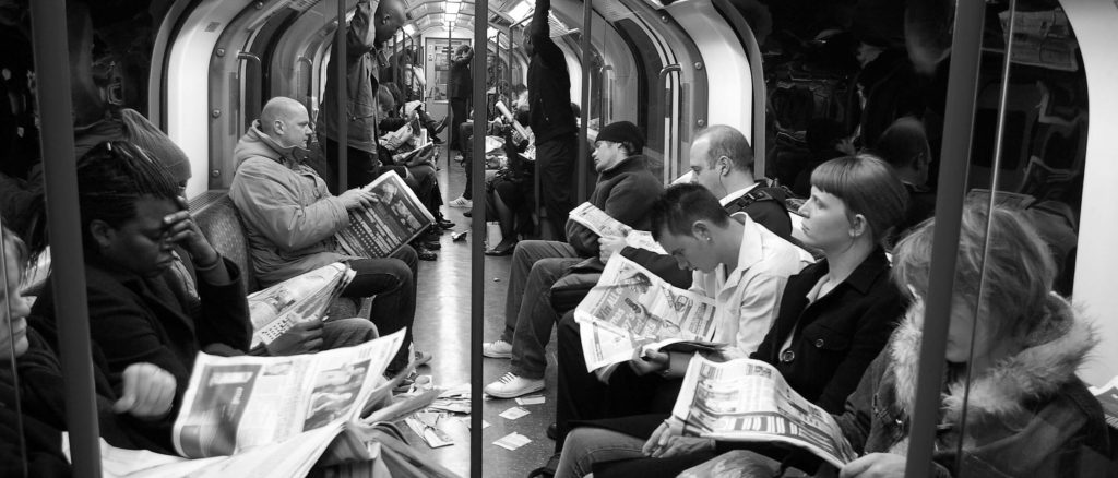 Subway riders reading newspapers